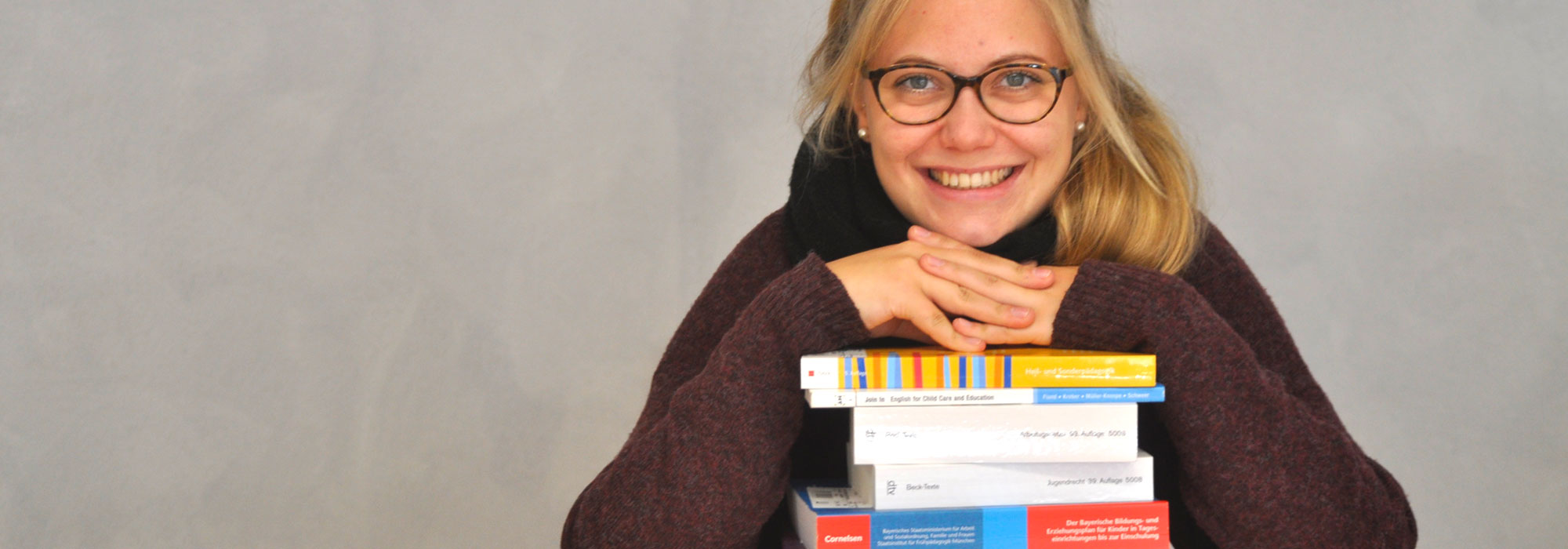 3_Symbolfoto_Bücherstapel-mit-Studierender